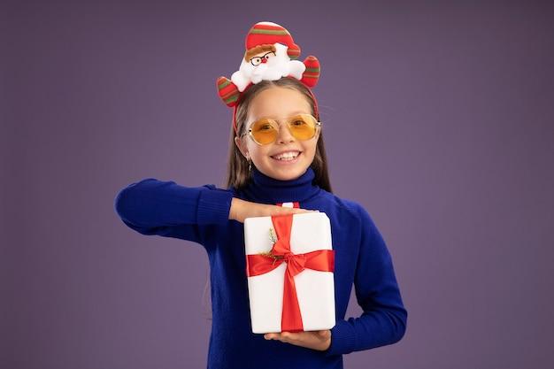 Menina com gola olímpica azul com gravata vermelha e aro de natal engraçado na cabeça segurando um presente com um sorriso no rosto feliz e alegre em pé sobre a parede roxa