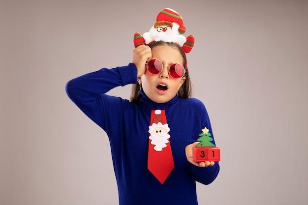 Menina com gola olímpica azul, usando um aro de natal engraçado na cabeça, segurando cubos de brinquedo com feliz ano novo, surpresa e confusa em pé sobre uma parede branca