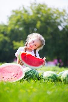 Menina com grande fatia de melancia no verão no parque. criança, comida saudável.