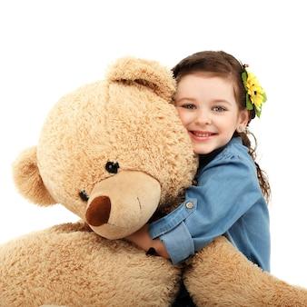 Menina com grande urso de pelúcia se divertindo rindo isolado no fundo branco
