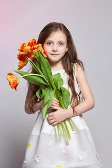 Menina com grandes olhos de anime azul e buquê de tulipa
