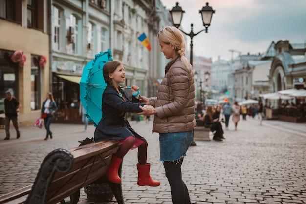 Menina com guarda-chuva e botas de borracha, se divertindo com a mãe dela