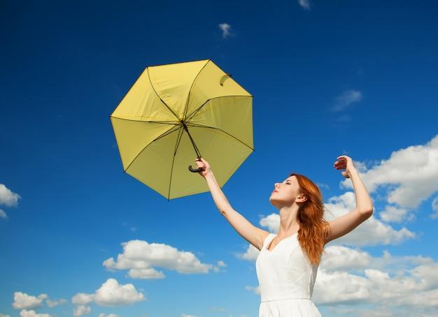 Menina com guarda-chuva no fundo do céu.