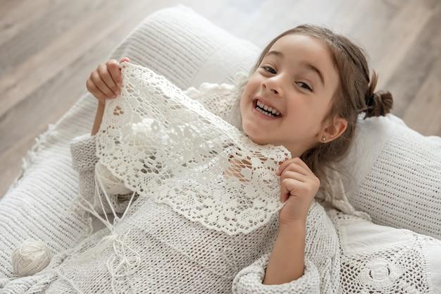 Menina com guardanapo de renda de fio de algodão natural, crochê à mão. fazer crochê como hobby.