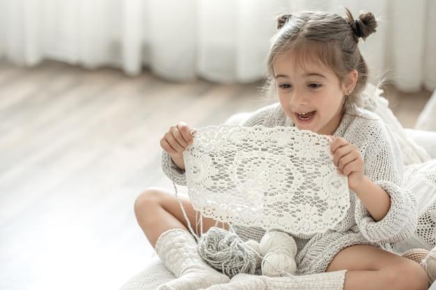 Menina com guardanapo de renda de fio de algodão natural, crochê à mão. fazer crochê como um hobby.