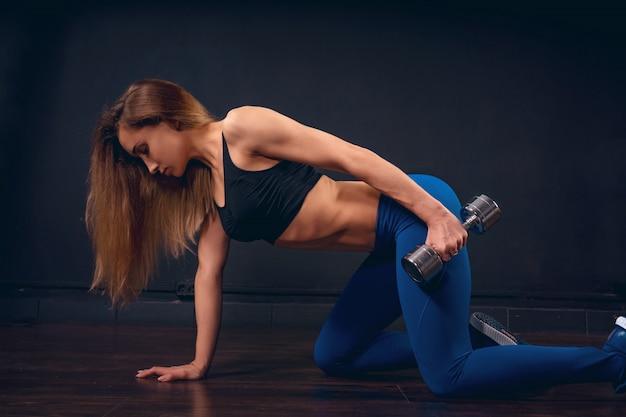 Menina com halteres fazendo exercícios para o tríceps de joelhos, inclinando a mão no chão estende o braço ao longo do corpo