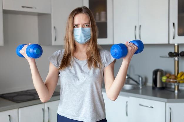 Menina com halteres na cozinha usando máscara protetora
