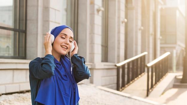 Menina com hijab ouvindo música com fones de ouvido