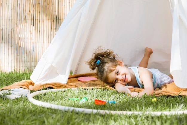 Menina com hula hoop deitada na barraca