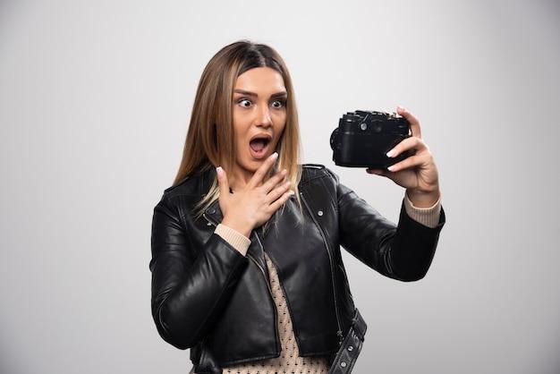 Menina com jaqueta de couro tirando fotos em posições engraçadas e estranhas