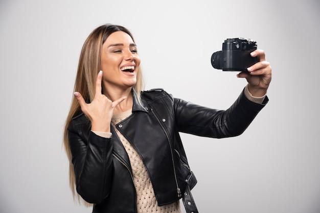 Menina com jaqueta de couro tirando suas fotos em posições elegantes e positivas.