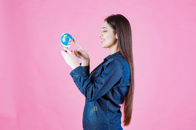 Menina com jaqueta jeans adivinhando lugares no globo