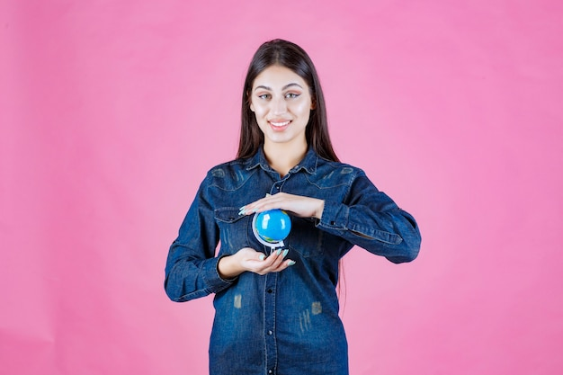 Menina com jaqueta jeans segurando um globo terrestre entre as mãos