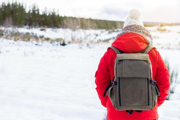Menina com jaqueta vermelha, chapéu e mochila, olhando para a paisagem nevada das florestas e montanhas em uma excursão. sensação de liberdade e tranquilidade. paz.