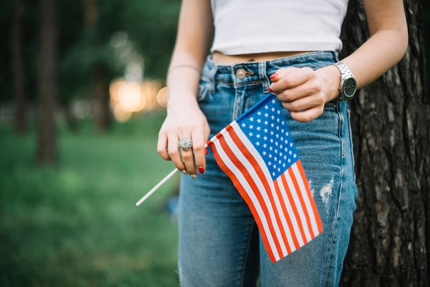 Menina com jeans e bandeira americana na natureza