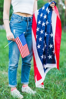 Menina com jeans e bandeiras americanas na natureza