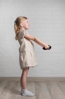 Menina com joystick nas mãos em casa