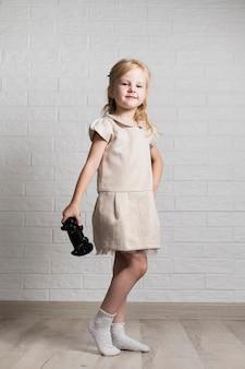 Menina com joystick posando para a câmera