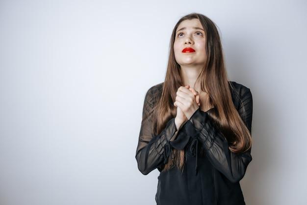 Menina com lábios vermelhos e uma blusa está rezando pedindo por isso