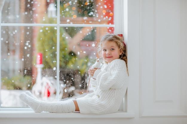 Menina com laço vermelho de natal sentada perto da grande janela segurando um pequeno rato branco