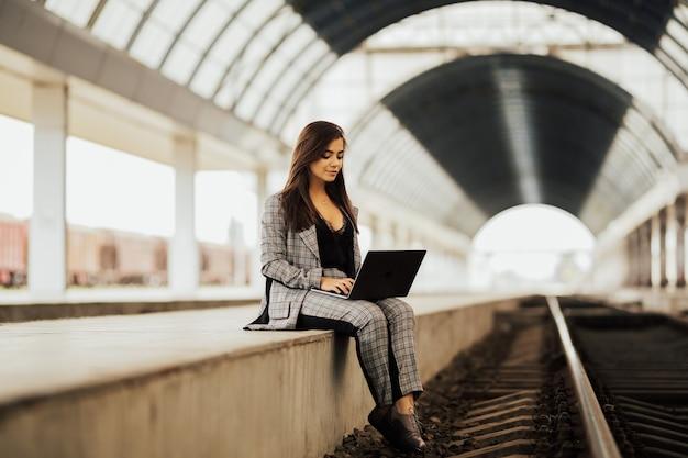Menina com laptop na estação.