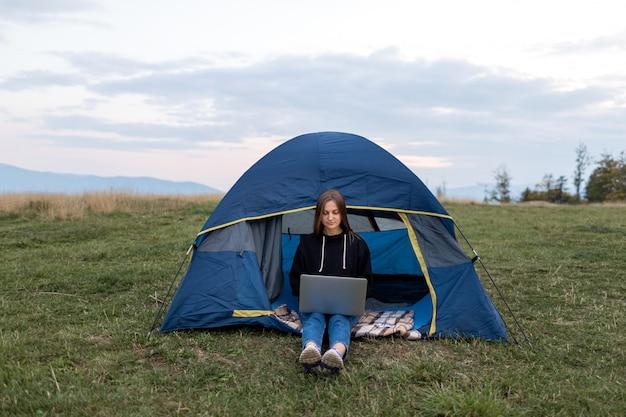 Menina com laptop nas montanhas. mulher turista usa um laptop na natureza,