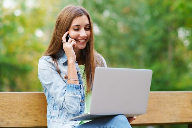 Menina com laptop no parque falando ao telefone