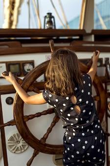 Menina com leme para barco