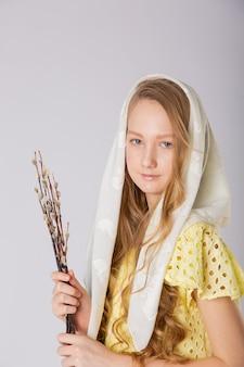 Menina com lenço branco na cabeça e salgueiro nas mãos