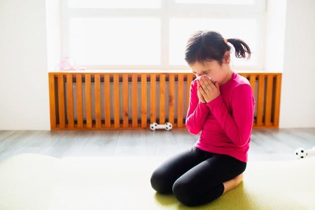 Menina com lenço e corrimento nasal. garoto bonito está treinando em um tapete interior. a modelo feminina de cabelos escuros no sportswear tem exercícios perto da janela no quarto dela.