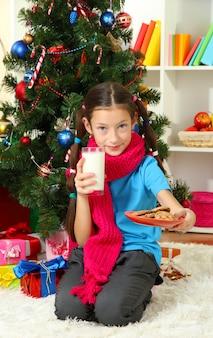 Menina com lenço rosa e copo de leite sentada perto da árvore de natal
