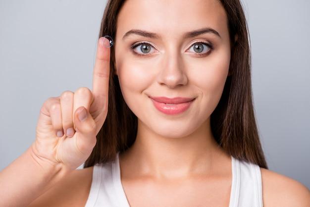 Menina com lentes de contato na mão