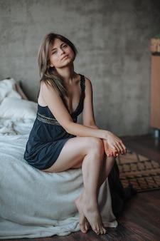 Menina com lindas pernas sentada na cama