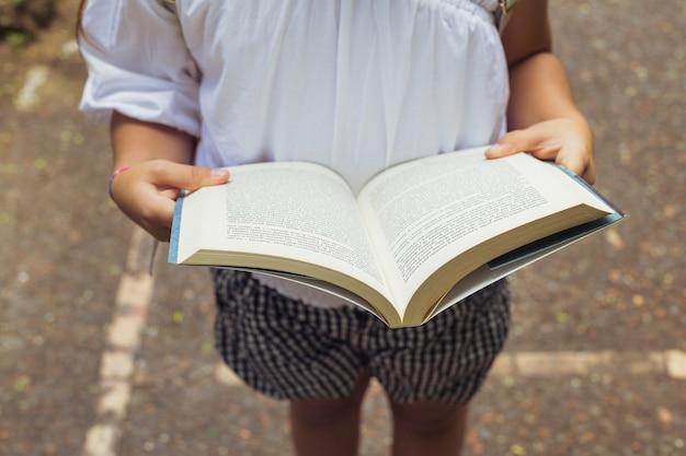 Menina, com, livro aberto, em, shorts