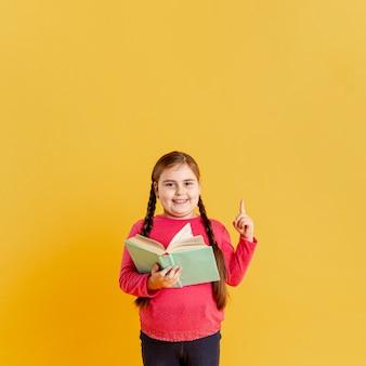 Menina com livro apontando acima
