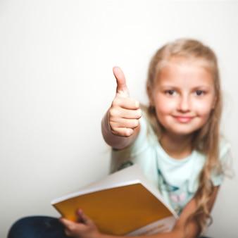 Menina com livro dando o polegar para cima, sorrindo
