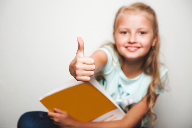 Menina com livro dando o polegar para cima sorrindo