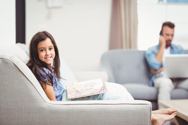Menina com livro de imagens enquanto pai em segundo plano