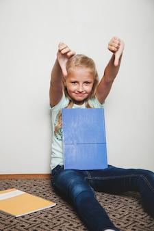 Menina com livros de texto sentado segurando os polegares para baixo