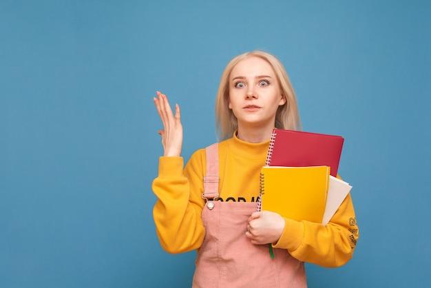 Menina com livros e cadernos nas mãos fica azul e parece infeliz na câmera