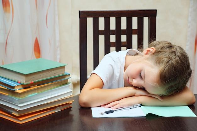Menina com livros parecendo cansada e apoiada nas mãos, sentada à mesa e estudando