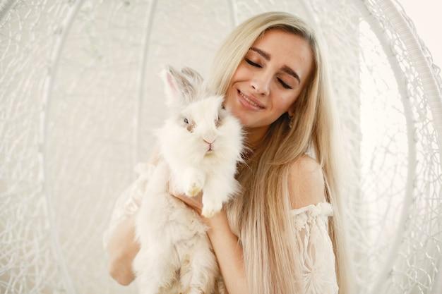 Menina com longos cabelos loiros com um coelho branco nos braços.
