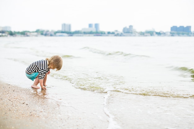 Menina com longos cabelos loiros soprando no vento andando na praia