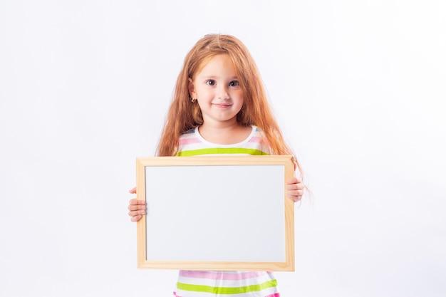 Menina com longos cabelos vermelhos sorrindo e segurando uma prancheta branca