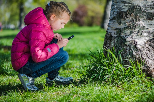 Menina com lupa olhando para o gramado