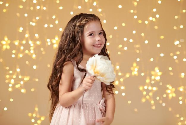 Menina com luzes de natal perto de fundo amarelo