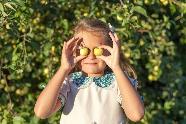 Menina com maçã segurando na frente do rosto no pomar de maçãs. linda garota comendo maçã orgânica no pomar.