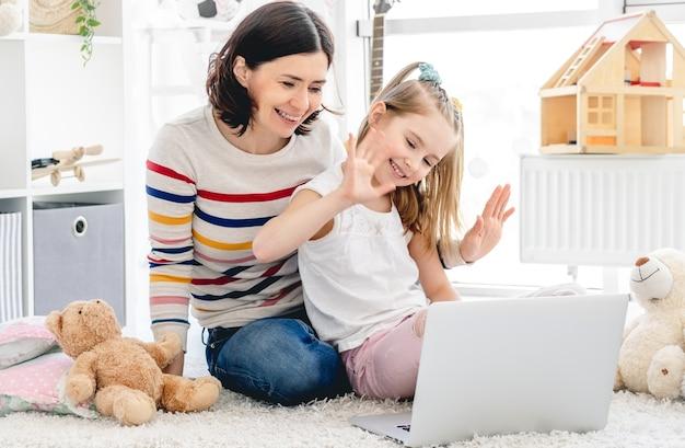 Menina com mãe fazendo videochamada