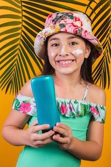 Menina com maiô e creme com protetor solar, sorrindo alegremente sobre fundo amarelo.