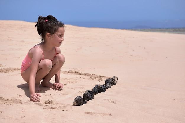 Menina com maiô rosa, brincando com a areia e pedras na praia